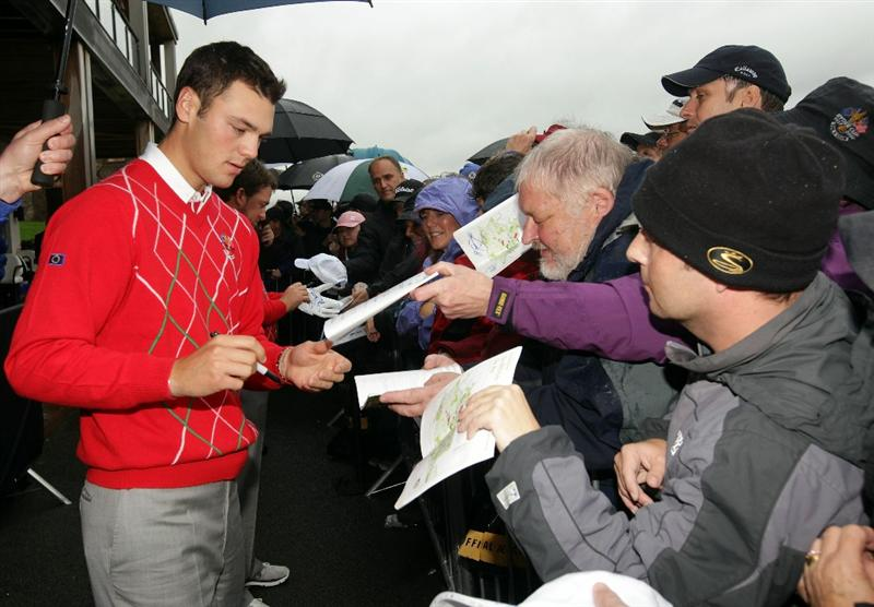 NEWPORT, WALES - OCTOBER 01:  Martin Kaymer of Europe signs autographs as rain falls and play is suspended during the Morning Fourball Matches during the 2010 Ryder Cup at the Celtic Manor Resort on October 1, 2010 in Newport, Wales.  (Photo by Andrew Redington/Getty Images)