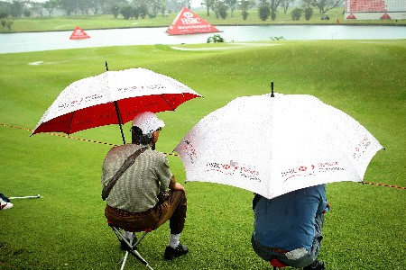 SINGAPORE - MARCH 02:  Golf Fans wait under umbrellas during the weather-delayed final round of the HSBC Women's Champions at Tanah Merah Country Club on March 2, 2008 in Singapore.  (Photo by Scott Halleran/Getty Images)