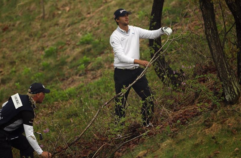 ICHEON, SOUTH KOREA - APRIL 30:  Rikard Karlberg of Sweden and his caddie remove a fallen branch on the first hole during the third round of the Ballantine's Championship at Blackstone Golf Club on April 30, 2011 in Icheon, South Korea.  (Photo by Andrew Redington/Getty Images)