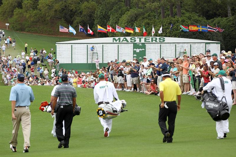 AUGUSTA, GA - APRIL 08:  Tiger Woods, Matt Kuchar and K.J. Choi of Korea walk off the first tee with their caddies during the first round of the 2010 Masters Tournament at Augusta National Golf Club on April 8, 2010 in Augusta, Georgia.  (Photo by Jamie Squire/Getty Images)