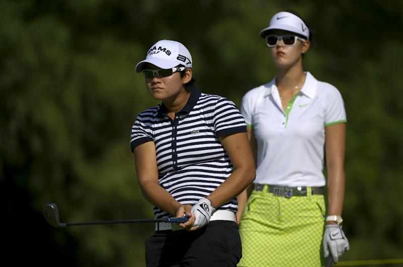 ROGERS, AR - SEPTEMBER 10:  Yani Tseng of Taiwan makes a tee shot as Michelle Wie looks on during the first round of the P&G NW Arkansas Championship at the Pinnacle Country Club on September 10, 2010 in Rogers, Arkansas.  (Photo by Robert Laberge/Getty Images)