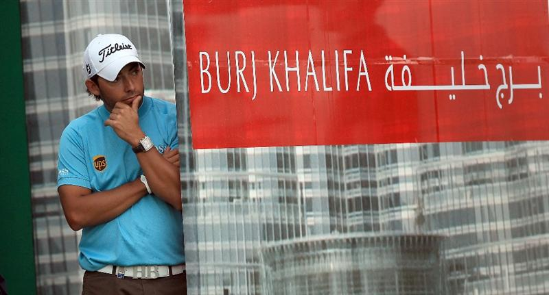 DUBAI, UNITED ARAB EMIRATES - FEBRUARY 06: Pablo Martin of Spain peers around the hoardings at the back of the 18th green watching Miguel Angel Jimenez of Spain during the third round of the 2010 Omega Dubai Desert Classic on the Majilis Course at the Emirates Golf Club on February 6, 2010 in Dubai, United Arab Emirates.  (Photo by David Cannon/Getty Images)