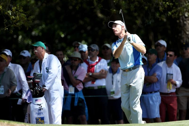 AUGUSTA, GA - APRIL 07:  Jim Furyk watches a shot on the first hole Adam Scott of Australia his caddie Mike Cowan looks on during the first round of the 2011 Masters Tournament at Augusta National Golf Club on April 7, 2011 in Augusta, Georgia.  (Photo by Andrew Redington/Getty Images)