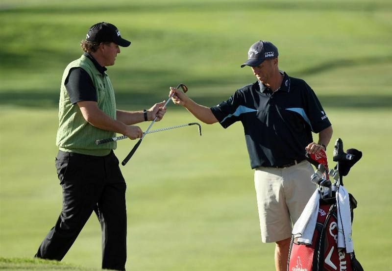 LA JOLLA, CA- JANUARY 26:  Phil Mickelson switches clubs with his caddie Jim 'Bones' Mackay after hitting out of the 17th green bunker during the Pro-Am at the Farmers Insurance Open at Torrey Pines on January 26, 2011 in La Jolla, California. (Photo by Donald Miralle/Getty Images)
