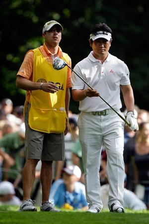 CHASKA, MN - AUGUST 16:  Y.E. Yang of South Korea (R) takes a club on the 14th tee from his caddie A.J. Montecinos during the final round of the 91st PGA Championship at Hazeltine National Golf Club on August 16, 2009 in Chaska, Minnesota.  (Photo by Jamie Squire/Getty Images)