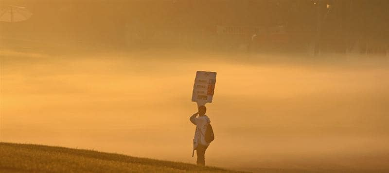 DUBAI, UNITED ARAB EMIRATES - FEBRUARY 01:  A scorbaord holder walks to position in the early morning mist during the completion of the third round of the 2009 Dubai Desert Classic on the Majilis Course at the Emirates Golf Club on February 1, 2009 in Dubai, United Arab Emirates  (Photo by David Cannon/Getty Images)