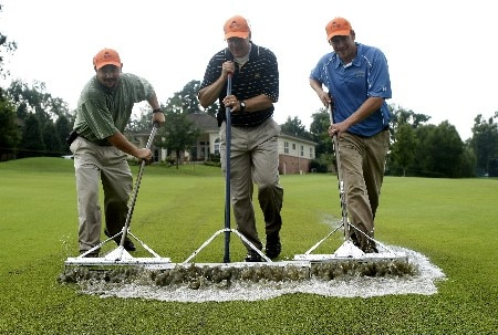 ROGERS, ARKANSAS - SEPTEMBER 7:  Course maintenance employees work to clear water from the fairway on the 5th hole during a rain delay before the start of the first round of the 2007 LPGA NW Arkansas Championship presented by John Q. Hammons at Pinnacle Country Club on September 7, 2007 in Rogers, Arkansas.  (Photo by Wesley Hitt/Getty Images)