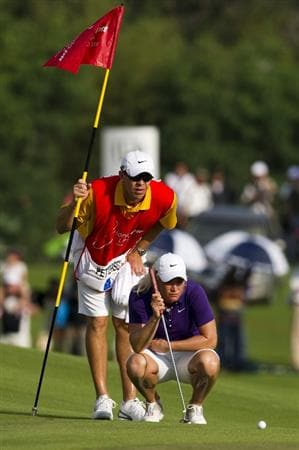 CHON BURI, THAILAND - FEBRUARY 21:  Suzann Pettersen of Norway and her caddy Dave Brooker lines up a putt on the 18th green during the final round of the Honda PTT LPGA Thailand at Siam Country Club on February 21, 2010 in Chon Buri, Thailand.  (Photo by Victor Fraile/Getty Images)