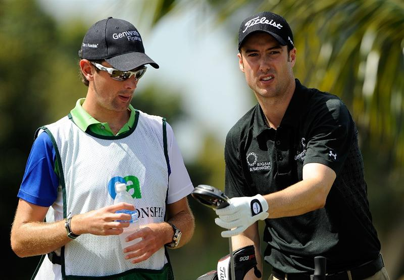 DORAL, FL - MARCH 15:  Ross Fisher (R) of England and his caddie look over a shot during the final round of the World Golf Championships-CA Championship at the Doral Golf Resort & Spa March 15, 2009 in Miami, Florida.  (Photo by Sam Greenwood/Getty Images)