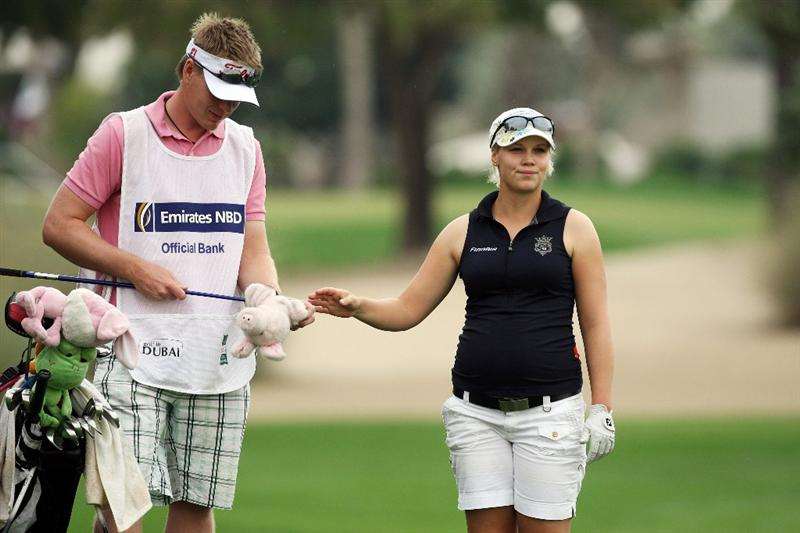 DUBAI, UNITED ARAB EMIRATES - DECEMBER 11:  Minea Blomqvist of Finland takes her club from her boyfriend caddie Roope Kakko of Finland before she plays her second shot at the 10th hole during the third round of the Dubai Ladies Masters, on the Majilis Course at the Emirates Golf Club on December 11, 2009 in Dubai, United Arab Emirates.  (Photo by David Cannon/Getty Images)