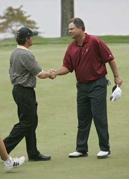 Kenny Perry of the U.S. team, right, congratulates Mark Hensby of the International team after Perry won their singles match in the final round of The Presidents Cup at Robert Trent Jones Golf Club in Prince William County, Virginia on September 25, 2005.Photo by Stan Badz/PGA TOUR/WireImage.com