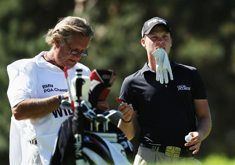 VIRGINIA WATER, ENGLAND - MAY 22:  Danny Willett of England takes advice from his caddie Malcolm Mason as he prepares to play his tee shot at the 8th hole during the third round of the BMW PGA Championship on the West Course at Wentworth on May 22, 2010 in Virginia Water, England.  (Photo by Ross Kinnaird/Getty Images)
