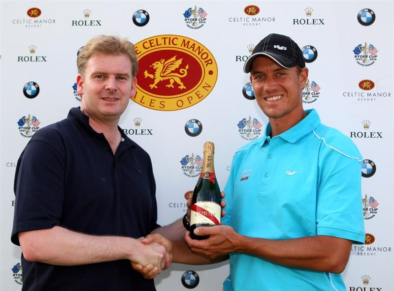 NEWPORT, WALES - JUNE 04:  Paul Williams, PR Manager for The Celtic Manor Resort presents Mads Vibe-Hastrup of Denmark a bottle of champagne for his hole in one on the 7th, during the first round of the Celtic Manor Wales Open on the 2010 Course at The Celtic Manor Resort on June 4, 2009 in Newport, Wales. There was three hole in one's made during the first round - Pablo Larazzabal and Mads Vibe Hastrup on the 7th and Jeev Milkha Singh on the 13th.  (Photo by Richard Heathcote/Getty Images)