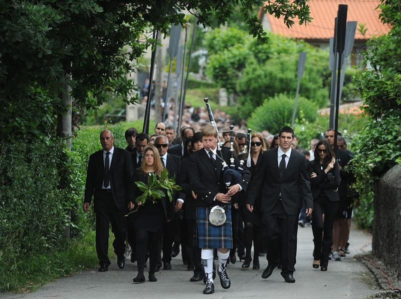 PEDRENA, SPAIN - MAY 11:  A lone piper and the local rowing club head the procession to San Pedro church during the funeral service held for legendary Spanish golfer Seve Ballesteros on May 11, 2011 in Pedrena, Spain. Top-ranked golf players have joined family members and friends to pay their last respects to the late golf great, who died on May 7, 2011 from complications arising from a brain tumor, in his home town parish church.  (Photo by Denis Doyle/Getty Images)
