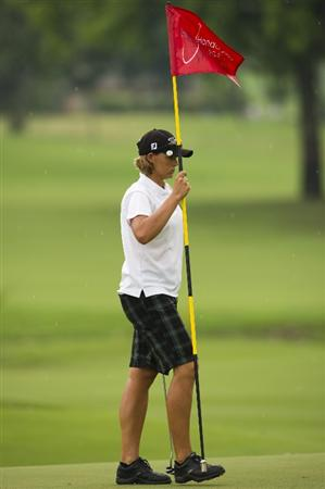 CHON BURI, THAILAND - FEBRUARY 20:  Katherine Hull of Australia holds the flag on the 15th green during round three of the Honda PTT LPGA Thailand at Siam Country Club on February 20, 2010 in Chon Buri, Thailand.  (Photo by Victor Fraile/Getty Images)