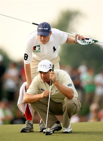 DUBAI, UNITED ARAB EMIRATES - NOVEMBER 20:  Padraig Harrington of Ireland lines up a putt with his caddie Ronan Flood on the 17th hole during the second round of the Dubai World Championship on the Earth Course, Jumeirah Golf Estates on November 20, 2009 in Dubai, United Arab Emirates.  (Photo by Andrew Redington/Getty Images)